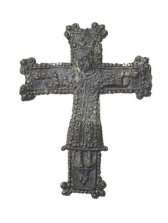 Pilgrim badge from an unknown shrine in the form of a crucifix. The edges of the cross are beaded and there are trefoils at each corner of the limbs of the cross. Christ is shown wearing a crown and a long robe with a belt around the waist. This is the typical way that Christ on the cross was depicted before the 11th century so this badge probably commemorates an early medieval rood. 15th century | Museum of London