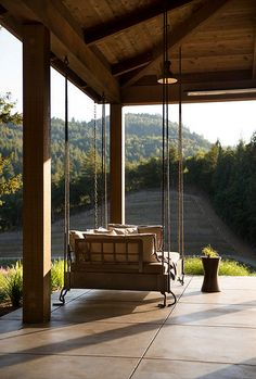 Farmhouse porch with rustic reclaimed wood swing vineyard view. Jennifer Robin Interiors. Paul Dyer Photography.