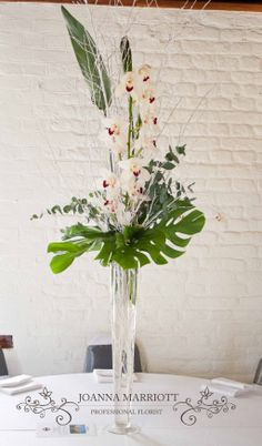 Winter theme wedding table arrangement. White cymbidium, green and grey foliage, white twigs with silver glitter arranged in a tall vase.