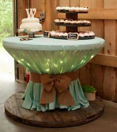 Big wooden spool with material and burlap bow.