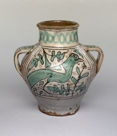Bulbous jar, cylindrical neck, flanged rim; two fat strap handles. Reddish earthenware covered with a greyish, presumed tin glaze and painted in manganese and green. Either side is a standing bird amid oak leaf sprays. Round the neck a cable pattern in green. Interior has a brownish glaze.
