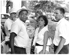 "Standing with local civil rights leader J.C. Fairley, President of the Forrest County NAACP, are Freedom Summer volunteers (left to right) Bob ""Soda Pop"" Ehrenreich, Patricia Yorck (Port Washington, New York; a refugee from Nazi Germany; Freedom School teacher), Terri Shaw (Buffalo, Communications Director Hattiesburg project), and Doug Tuchman (New York City; Freedom School teacher). Taken at the fish fry given for the volunteers by local civil rights leader Vernon Dahmer on Independence Day."