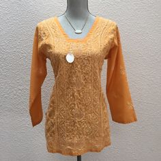 Handmade hand-embroidered tunic (made in India) Just here from India. Beautiful handmade and embroidered tunic in a lovely orange sherbet color. Opaque sequin detailing throughout and lovely sculpted neckline. Straight body cut. Slits on side at hips. fits a size small. 100% cotton. Handmade Tops Tunics