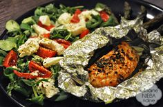 Salmon baked on green asparagus with sesame seeds and onions scallions