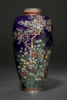 A CLOISONNÉ VASE  MARK OF THE HAYASHI KODENJI STUDIO, MEIJI PERIOD (LATE 19TH CENTURY)  Worked in various thicknesses of silver wire and coloured enamels on a dark blue ground with a maple tree among a profusion of flowers including tiger lilies, chrysanthemums, irises, wild pinks and grasses, silver and copper mounts 21cm. high
