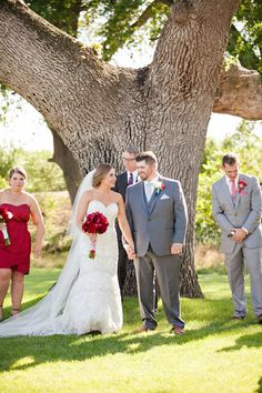 Red bridesmaid dresses with red roses and gray suits. Classic and perfect.