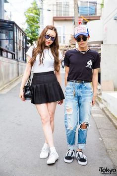 Emu, a model, is wearing a black and white ensemble which consists of white ribbed shirt and black, pleated satin skirt, both from American Apparel. White N. HOOLYWOOD x Vans canvas sneakers and a black, mini-satchel handbag completed her ensemble. Her accessories – from Chrome Hearts and Omega – include black sunglasses, a black bow necklace, a silver watch and silver rings.  S.You is wearing a black pocket t-shirt from Chrome Hearts, ripped jeans from Moussy, and Vans sneakers.