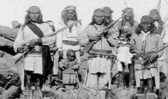 Chiricahua Adelnietze, Zhonne (with Nahbay's baby in front of him), Naiche, Fun. In the back, frorm left Hunlona, Mohtsos, and Chappo. Photo, C. S. Fly,  1886.