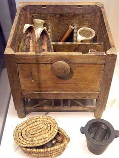 A fascinating Egyptian cosmetic box. It contains a pot, 2 vases, a pumice stone, a cosmetic dish, a pair of sandals and a kohl pot. It dates to about 1550 BC and was discovered in a tomb.