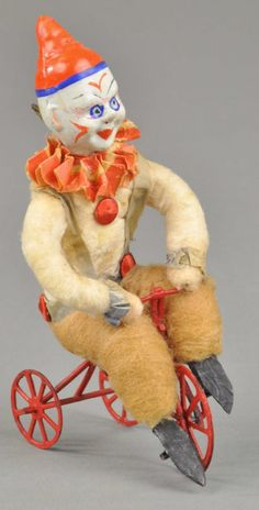 Clown riding tricycle. Spun cotton Christmas ornament with composition head.