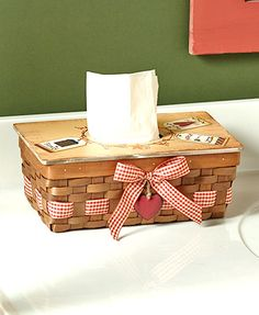 """Use this decorative piece to cover up your tissue box with a charming country design. Its woven look, gingham bow and metal ornament on the front add a rustic touch to any room. The lid opens up to fit most standard tissue boxes. Square, 5-1/4""""W x 5-1/2"""""""
