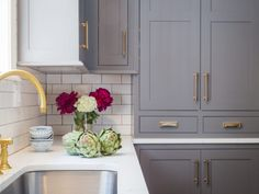 A curved stainless steel sink paired with an antique brass deck mount vintage faucet is fitted beneath a window to a white quartz countertop accenting cream dark gray cabinets fixed against a white subway backsplash. Purple Kitchen Cabinets, Refacing Kitchen Cabinets, Kitchen Cabinet Hardware, Kitchen Cabinet Colors, Grey Cabinets, Glass Cabinets, Brass Hardware, Kitchen Storage, Antique Brass Kitchen Faucet