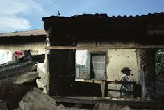 A sapeur named Lamame leaves his home, which has remained in poor condition since the last civil war (1997-2001), to show off in his neighborhood on a Sunday afternoon.