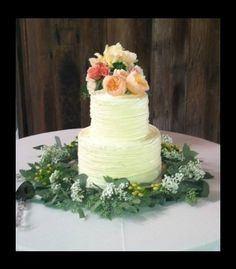 Simple buttercream two tiered wedding cake with fresh flowers