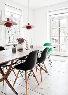 I love a minimal white look; this dining room has gorgeous black chairs, a thin wood table, and the setting is so light and fresh / White Home with Colorful Accents   79 Ideas
