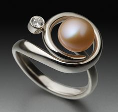 This ring is made from a sterling silver fork. Using fork tines that are wrapped around a natural pink pearl with added cubic zirconia (CZ) stone.