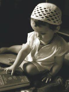 Muslim Little Boy Touches a Book of Quran