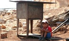 """Israel plans to demolish 13,000 Arab buildings in West Bank, UN Says""--A Palestinian boy sits in the shade while his family search for their belongings after their shack near Ramallah was demolished by the Israeli army. More than 11,000 demolition orders are still outstanding."