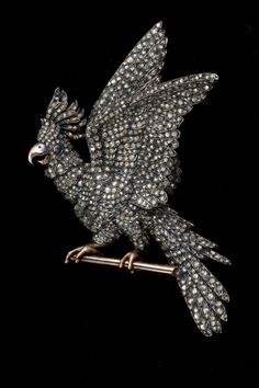 An antique diamond bird brooch in silver topped gold.
