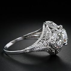 This ravishing and romantic treasure from the early 1900s elegantly presents a sparkling 1.59 carat antique cushion-cut diamond. The diamond is lovingly embraced by diamond-set crescents caressing tiny diamond-set hearts in this masterfully crafted and truly exquisite platinum and diamond Edwardian engagement ring. A gem!
