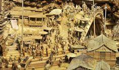 """Um momento da obra de  Zheng Chunhui. Este talentoso artista chinês passou os últimos quatro anos meticulosamente esculpindo uma réplica detalhada de uma famosa pintura tradicional chinesa chamada """"Ao longo do rio durante o Festival Qingming"""", em um tronco de árvore de pouco mais de 12 metros de comprimento."""