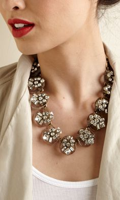 Mixed material necklace made up of floral-shaped clear glass stones, plastic and gold-toned metal. Includes an adjustable clasp closure.