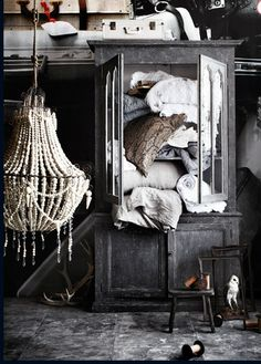 Chaotic decorating, luv this cabinet and the chandelier, my perfectionism would have to organize it though!