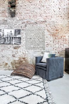 Exposed brick walls are lightly white washed to provide a more vibrant, cheerful look. Industrial modern decor is accented by a shaggy contemporary Moroccan rug with tassel. Love the gray fabric lounge chair. Modern Industrial Decor, Modern Decor, Industrial Rugs, Home Decor Colors, House Colors, My Living Room, Living Room Furniture, Atelier Loft, Brick In The Wall