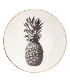 White/gold-colored. Small porcelain plate with gold-colored trim and a printed pineapple motif. Diameter 6 1/4 in.
