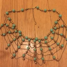 Blue beaded gold necklace Great condition! Worn once, just don't own anything that it matches with! Looks webbed when worn and it is a short necklace but fits great with low neck shirts especially! Vintage Jewelry Necklaces