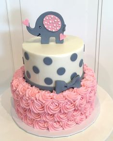 Baby shower cake with elephant on top. The cake is a pink rosette 2 tier with grey polka dots and bow on top tier.