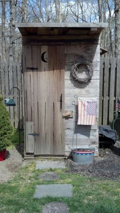 Outhouse garden shed. Mixed in among the evergreens? Cute!