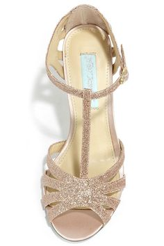 "Some enchanted evening starts with the Blue by Betsey Johnson Tee Champagne Glitter Dress Sandals! These stunning gold glitter heels have a strappy peep-toe upper with a T strap and adjustable ankle strap (with gold buckle). Wrapped 4.5"" stiletto heel rests on a blue single sole (perfect for brides-to be!). Cushioned insole. Rubber sole has nonskid markings. Available in whole and half sizes. Measurements are for a size 6. All man made materials."