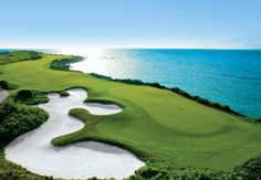 Emerald fairways rise above turquoise seas at the resort's 18-hole championship course designed by Greg Norman. #golf