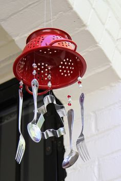 ♥A recycled cookie cutter and flatware hang winding in the wind beneath a red colander for a charming windchime.♥