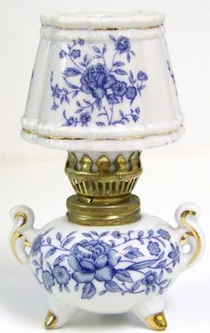 Antique Blue and White Miniature Oil Lamp with a pretty floral pattern of roses, vines and leaves. It is also adorned with gold on the lampshade and the feet of the base.