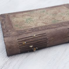 Rustic Wedding Guest Book or Photo Album Hand by EmersonBindery. This hand painted, country chic book can be used as either a photo album or guest book. On the cover is a floral panel I painted in subtle glimmering colors. I designed a textured and hand stamped frame around it and painted the book in rustic brown. Gold and brown beads embellish the threads along the spine. Handmade in NC. Available on Etsy.