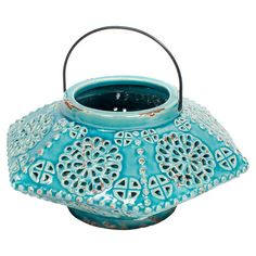 Weathered ceramic lantern in turquoise with handle and ornate openwork detail.