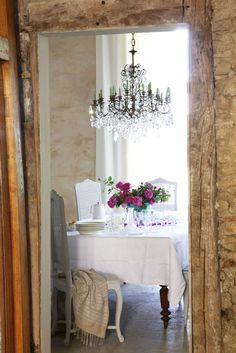 French country dining room // cane-back dining chairs, crystal chandelier, and a white tablecloth