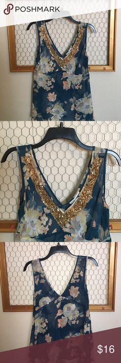 "Banana Republic floral sheer top with gold sequins Banana Republic floral sheer top with gold sequins. Beautiful dark teal with peach and yellow floral print and gold sequins. Size 4. Side zipper. 100% silk dry clean only.                                Pit to pit 16"". Length 26"".      It has a little pull as you can see on picture #5 Banana Republic Tops Tank Tops"