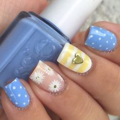 Check out this cute and cuddly nail art design in white, baby blue, baby pink and baby yellow polish with hints of flowers, polka dots and horizontal lines as details.