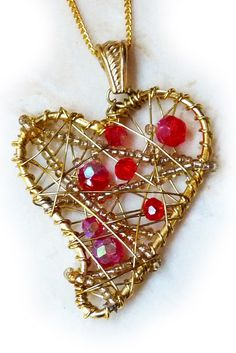 Whimsical abstract heart pendant. Made with lots of wire and seed beads to create a one-of-kind art heart. Bright red crystals nestle in the open wire work and add to the fun and festivity of this playful piece.