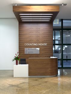 Reception desk and feature storage wall with light canopy finished in walnut veneer and corian. Made by Atmosphere