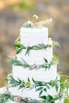 A rustic wedding cake decorated with flowers and greenery. Credits: Event Design & Planning by Fleur De Lis Event Consulting, Photography by The Veil Wedding Photography, Florals by Lori Parker Floral Studios, Cake by Kakes By Katie