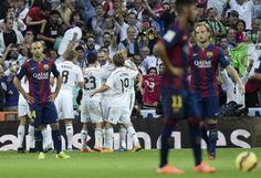 Pendant que les Madrilènes félicitent Karim Benzema, auteur du but du break, les Barcelonais, sonnés, semblent en proie au désespoir. (AFP/Gerard Julien)