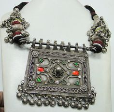 India    Antique silver amulet necklace.  The pendant is a symbol for family unity represented by a walled-in rectangle.  Strung on yarn with silver beads pendants.    Age not stated
