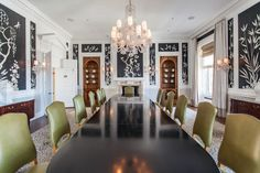 This San Francisco hotel dining room has a dark oval dining table, green chairs, open shelving, crown molding, chinoiserie wallpaper and a hanging light fixture.