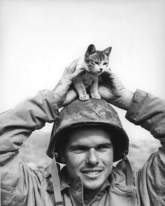 Corporal Edward Burckhardt, of Yonkers, New York, holding a kitten that he found at the base of Suribachi Yama on the battlefield at Iwo Jima when he came ashore with the 5th Marine Division, 1945.