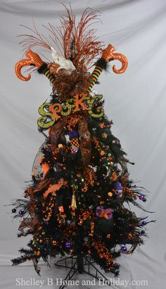 SHELLEY B GHOST TOP HALLOWEEN TREE  Decorate a tree for Halloween and give your witches, owls, and crows a place to haunt.  We decorated this 5 ft tree with items from our Halloween category.  Its filled with Halloween florals, witch and witch boot ornaments, and owl ornaments.  Feature decorations on the tree include witch leg stakes, Spooky dimensional sign, and a ghost figure.