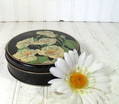 Vintage Floral Litho Black Metal Tin - White Flowers Printed Lid Canister - Art Deco Candy Box. $9.00, via Etsy.